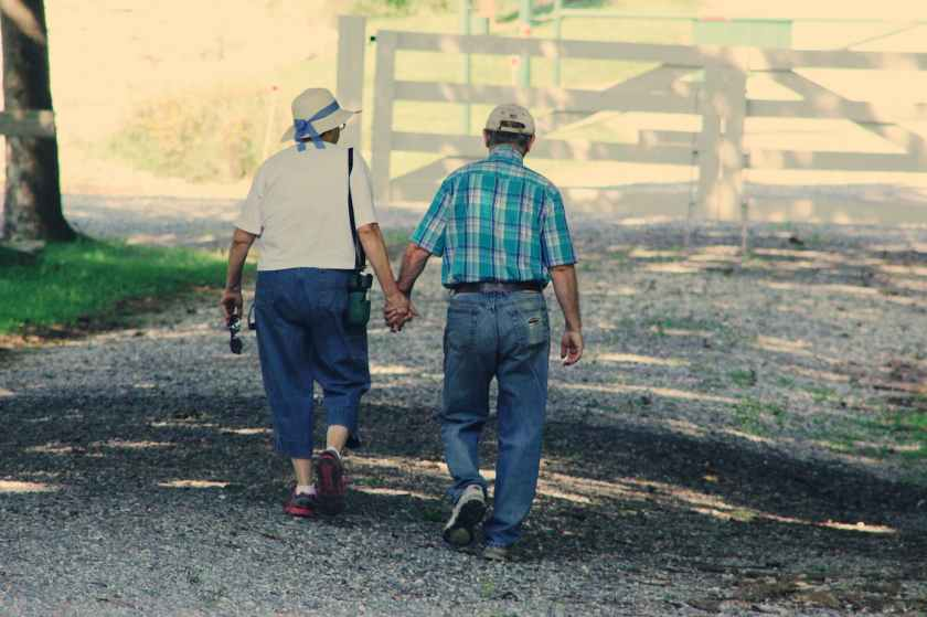 old couple walking while holding hands