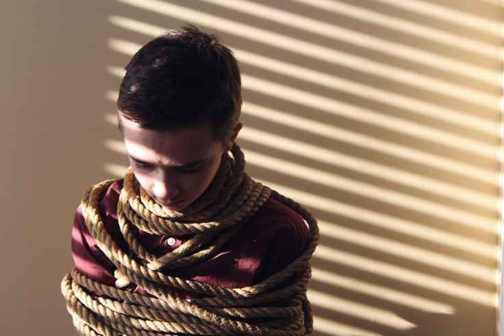 photo of a boy tied with ropes