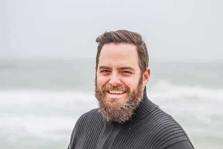 man wearing black zip up jacket near beach smiling at the photo